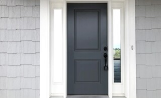 Charcoal Grey Front Door Surrounded by White Trip and Greige Shingle Siding