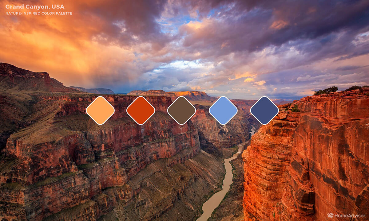 Photo of The Grand Canyon at sunset. Clouds and rocks are fire red and orange. Sky fades to blues and purples.
