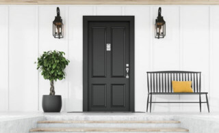 dark front door against white house next to tree, sconces and a metal bench