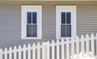 two double-hung windows behind a picket fence