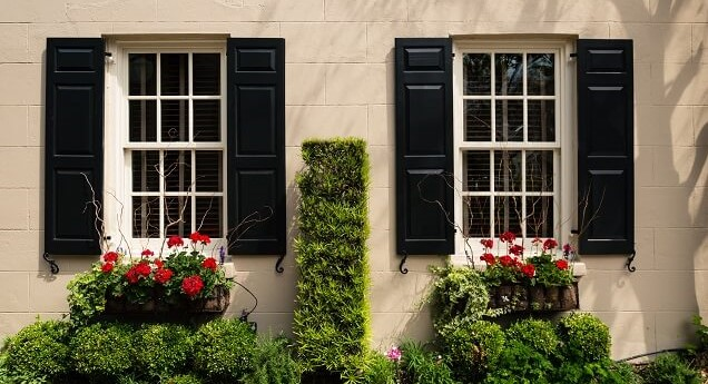 black exterior shutters on a cream-colored house