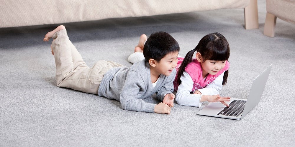kids play on computer on a carpet in room