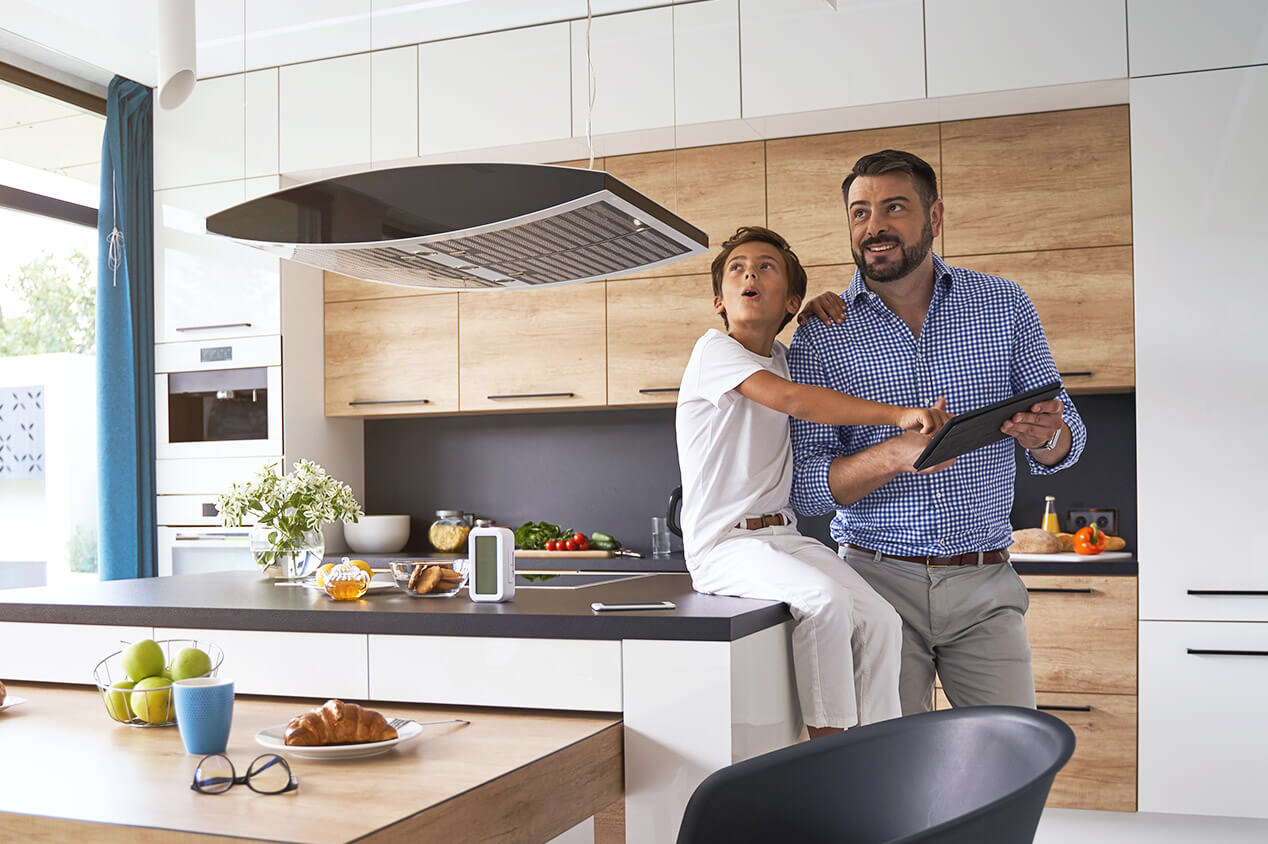 Father and child setting up smart home devices in modern remodeled kitchen