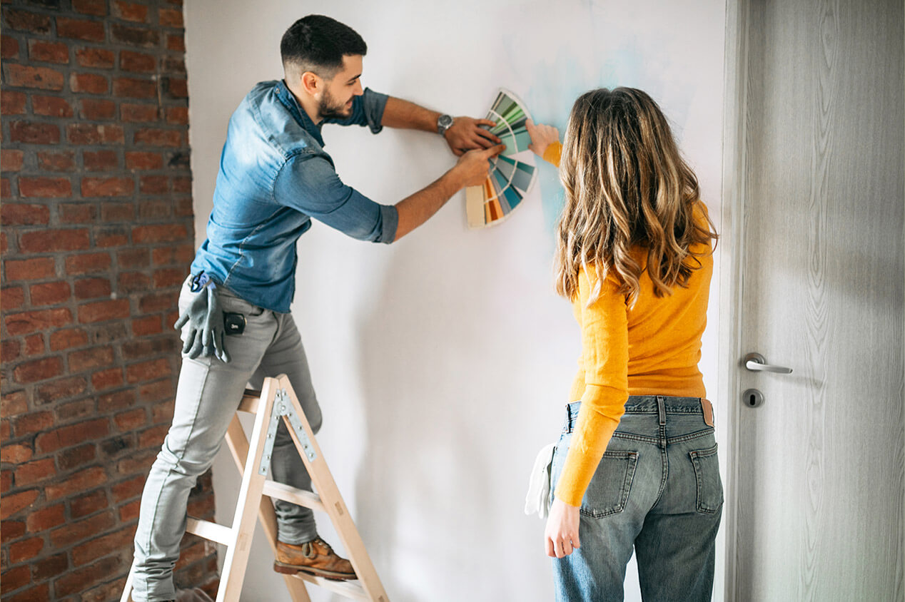 Couple choosing paint colors from a sample wheel