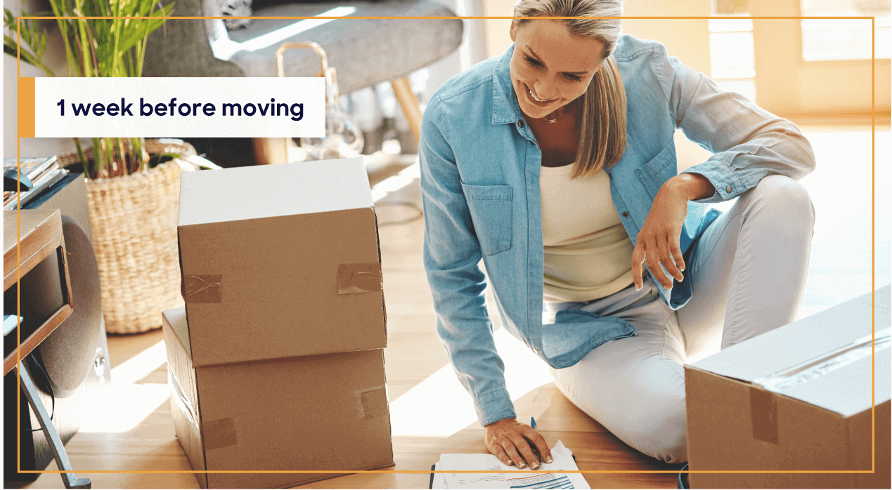 woman with a checklist surrounded by moving boxes