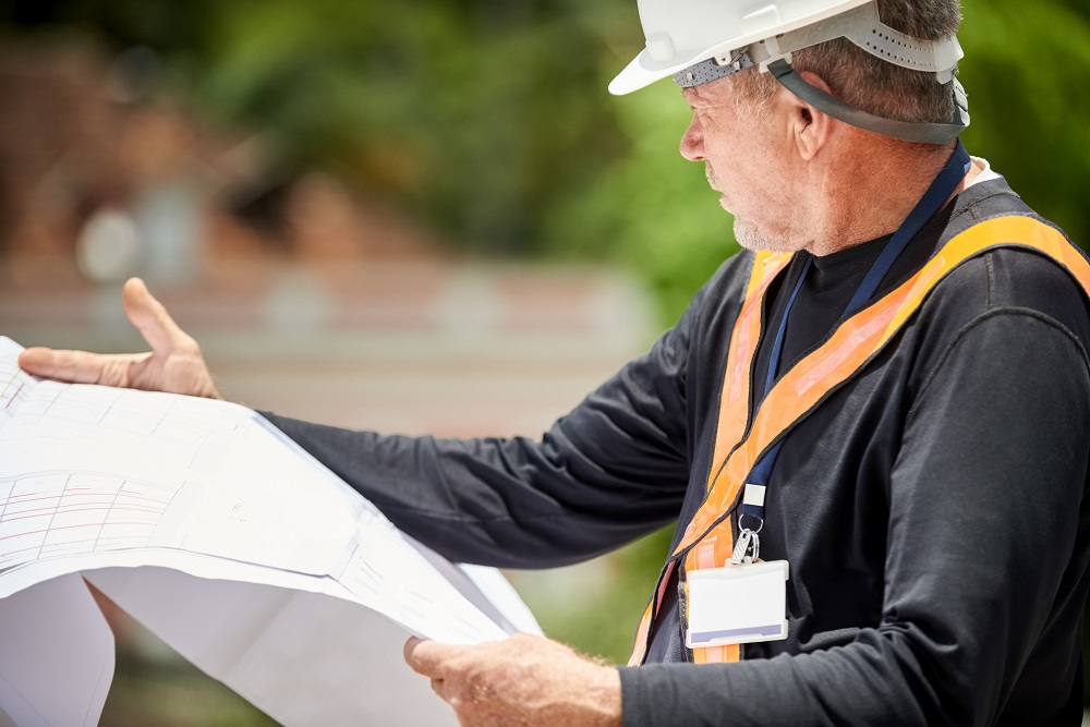 Shot of a senior construction engineer with building blueprint at site