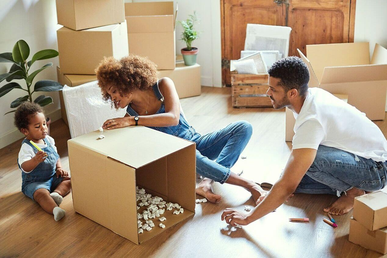 family of three moving with boxes