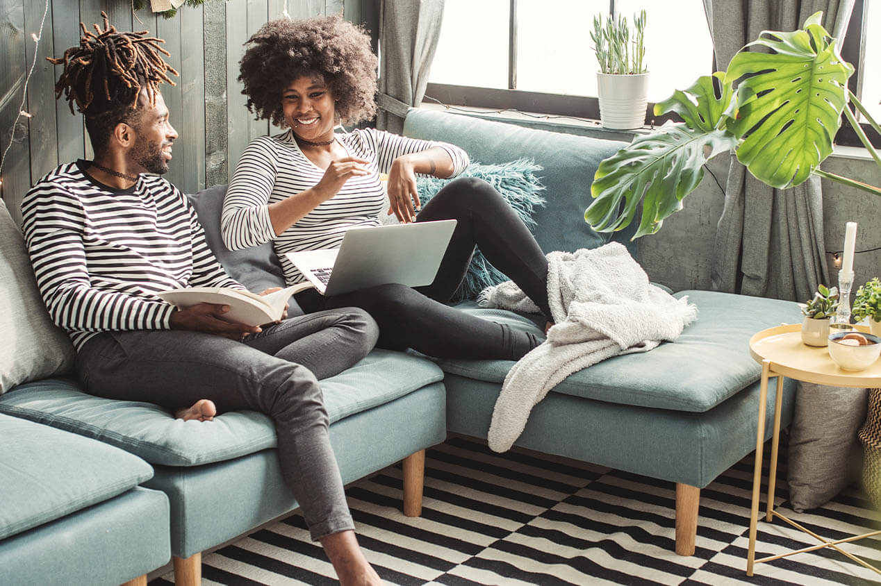 couple laughs in comfortable home while doing research