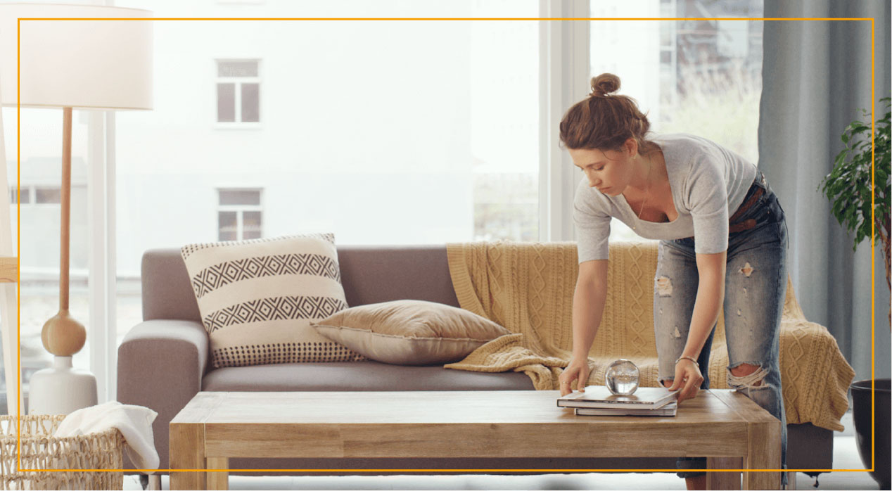 Woman organizing coffee table in living room