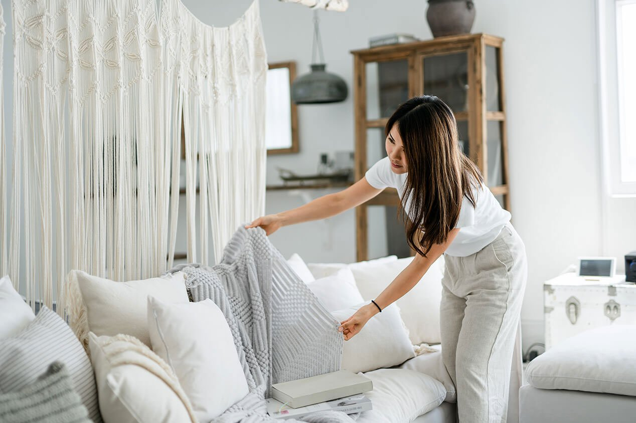 Woman placing blanket over couch