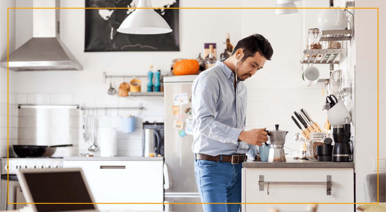 Man in kitchen pouring coffee out of French press