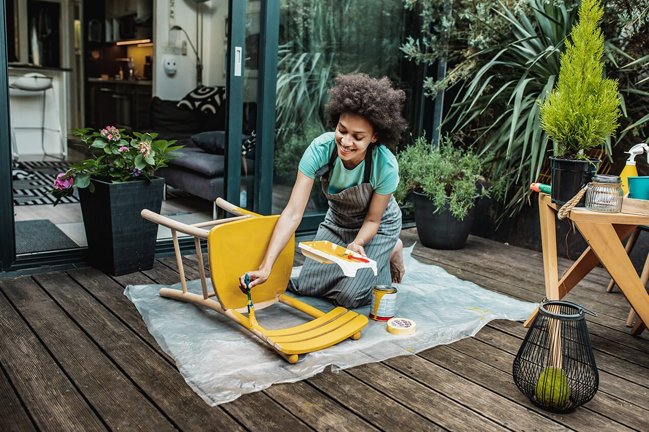 Young woman repainting wooden chair on patio