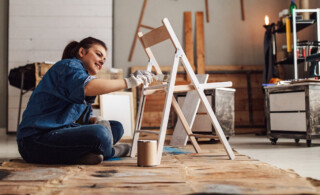 woman painting chair in garage