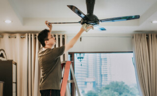 man cleaning ceiling fan