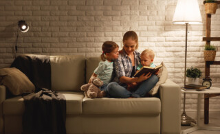mother reading to children on couch