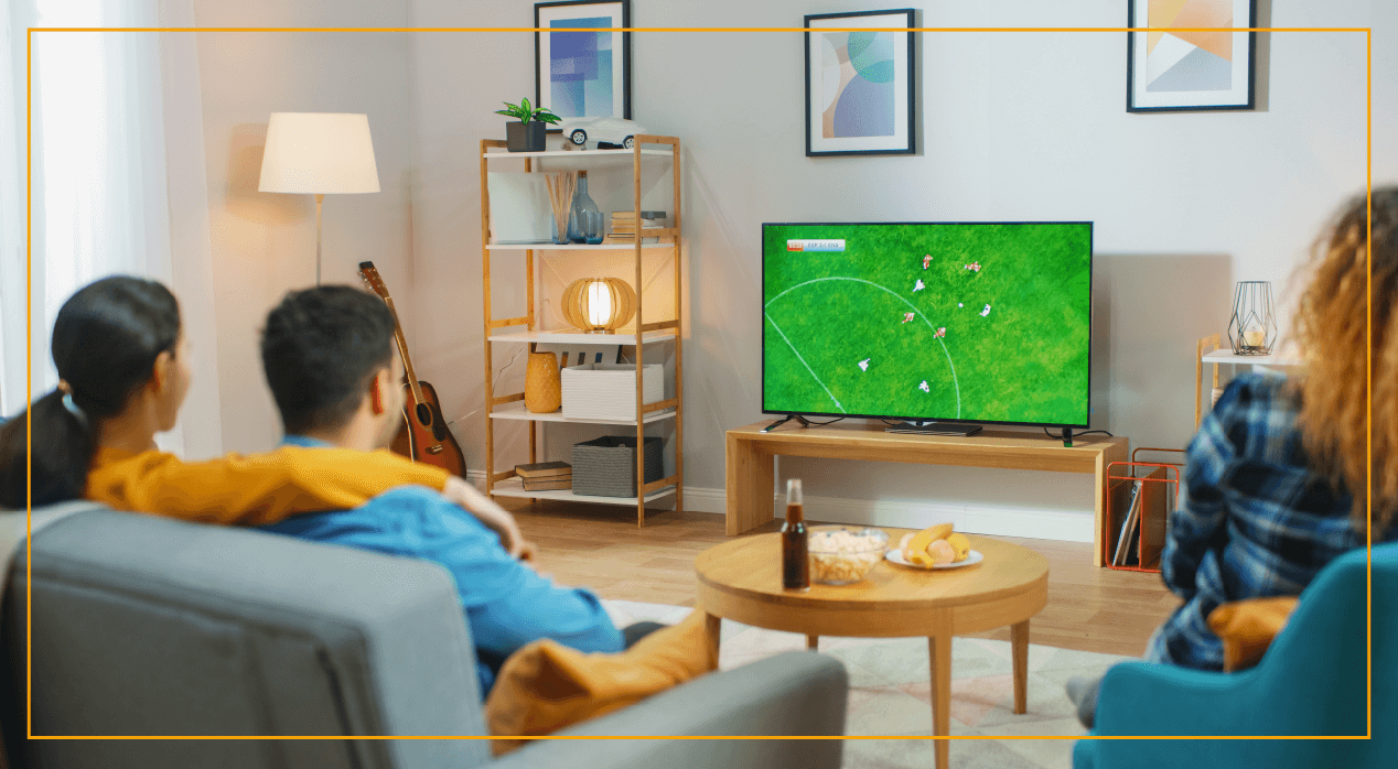 people in living room watching soccer on TV