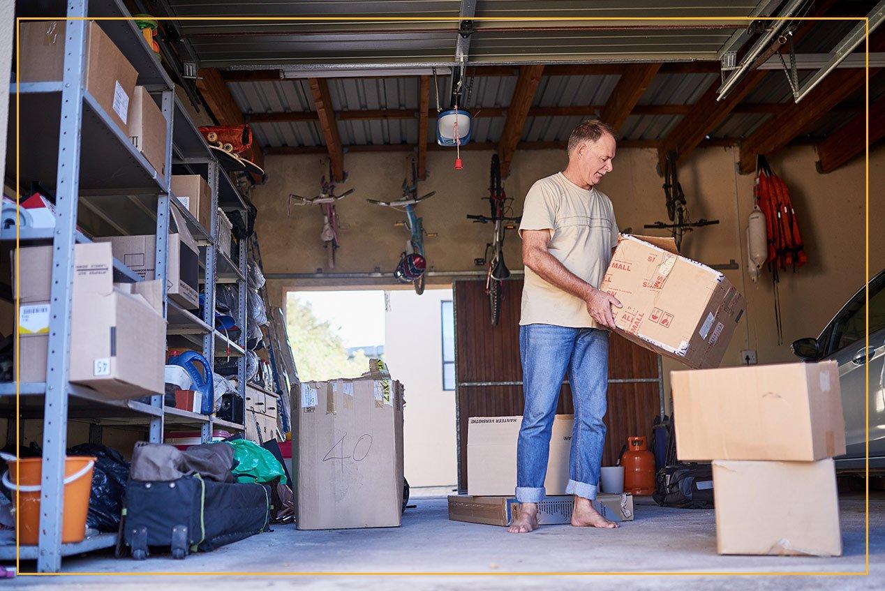 man in garage lifting boxes