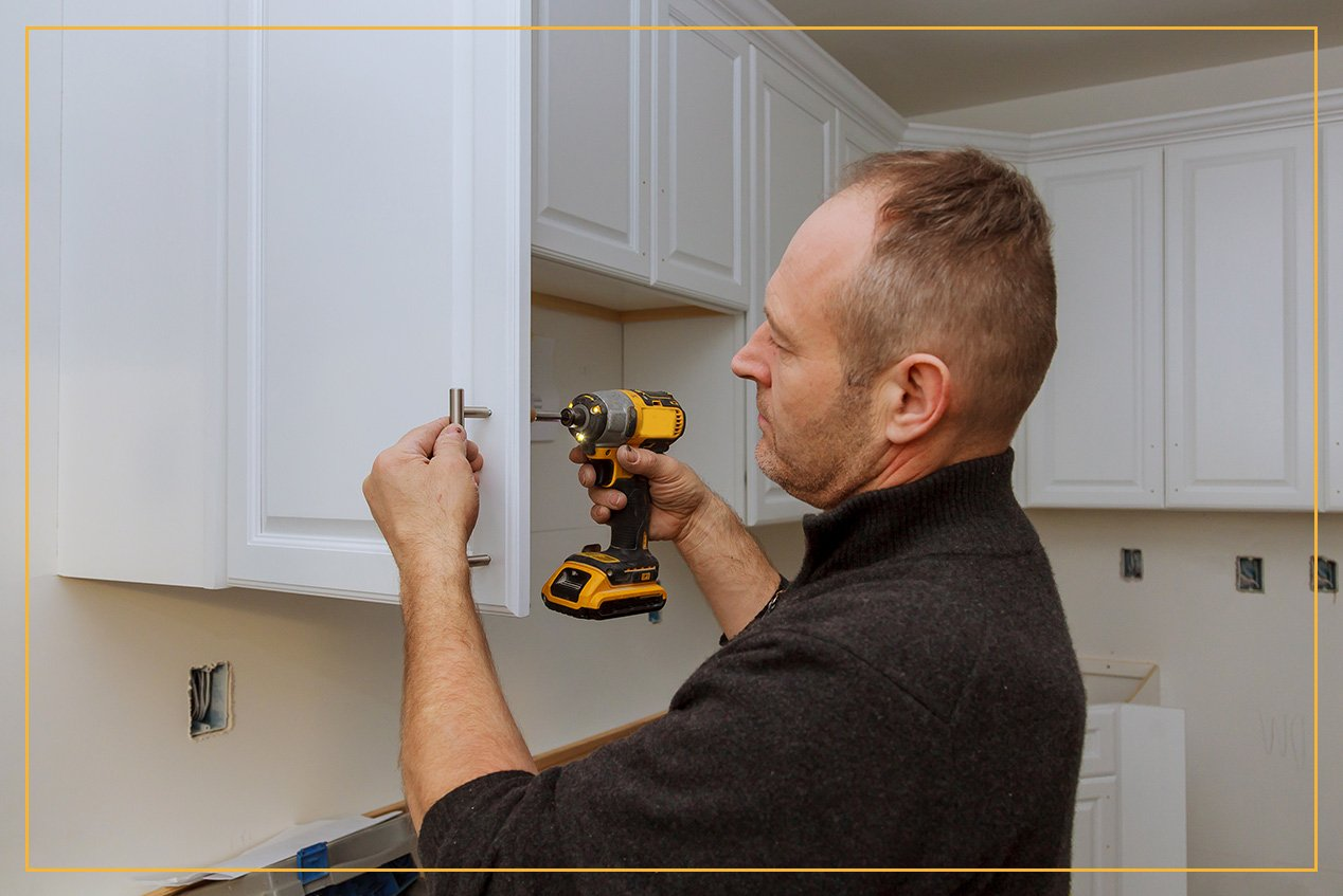 man installing cabinet hardware