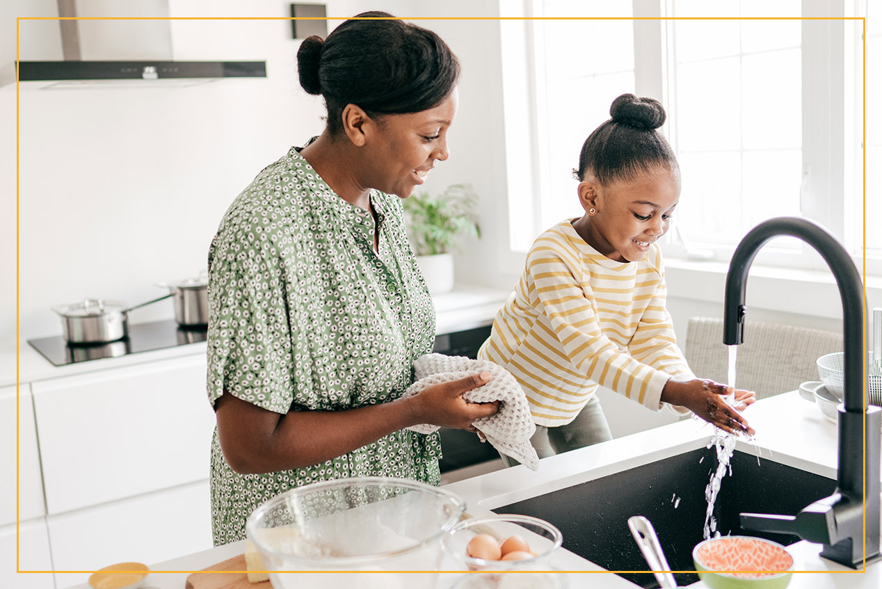 mom and daughter using sink in kitchen