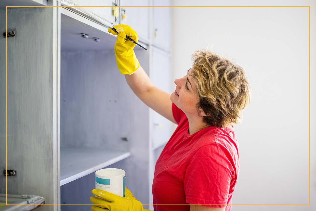 woman painting cabinet