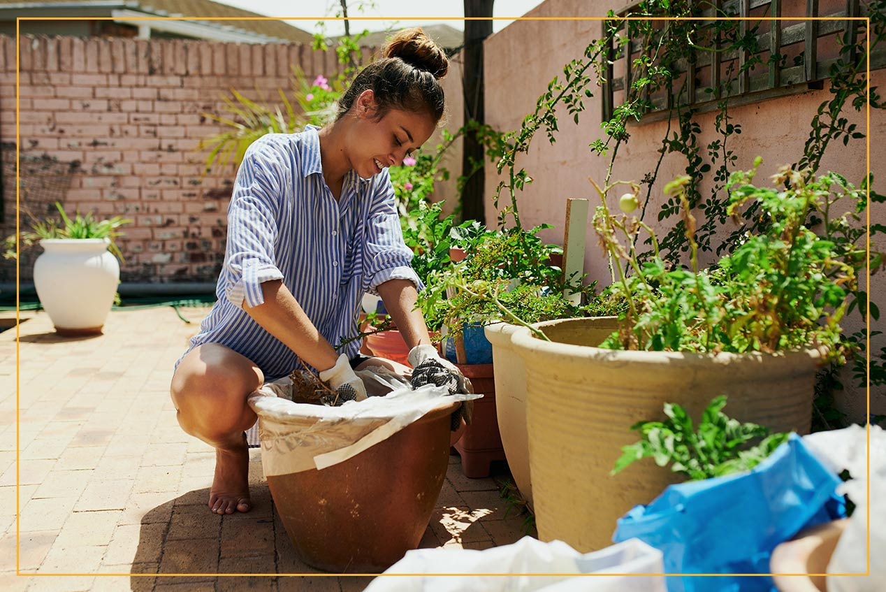 woman potting plants on back patio