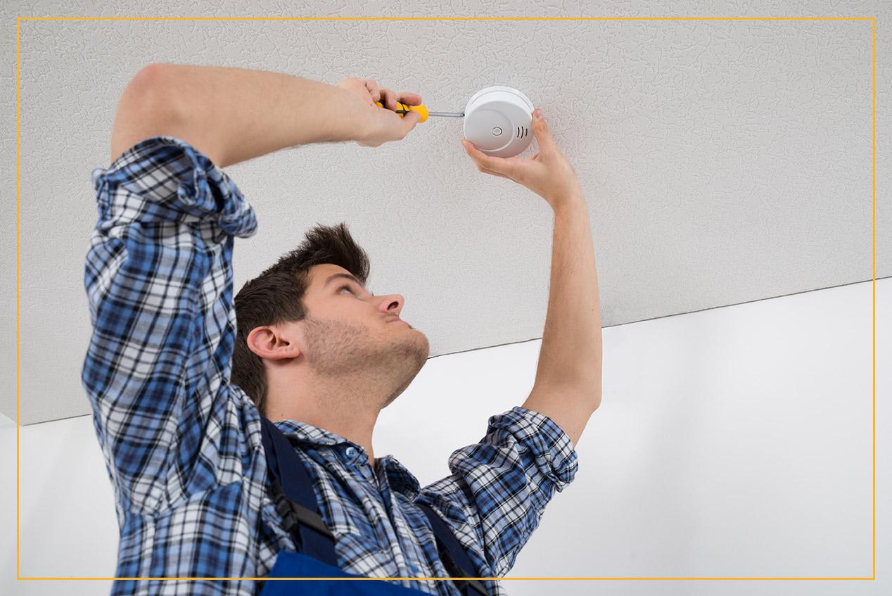 worker installing smoke detector
