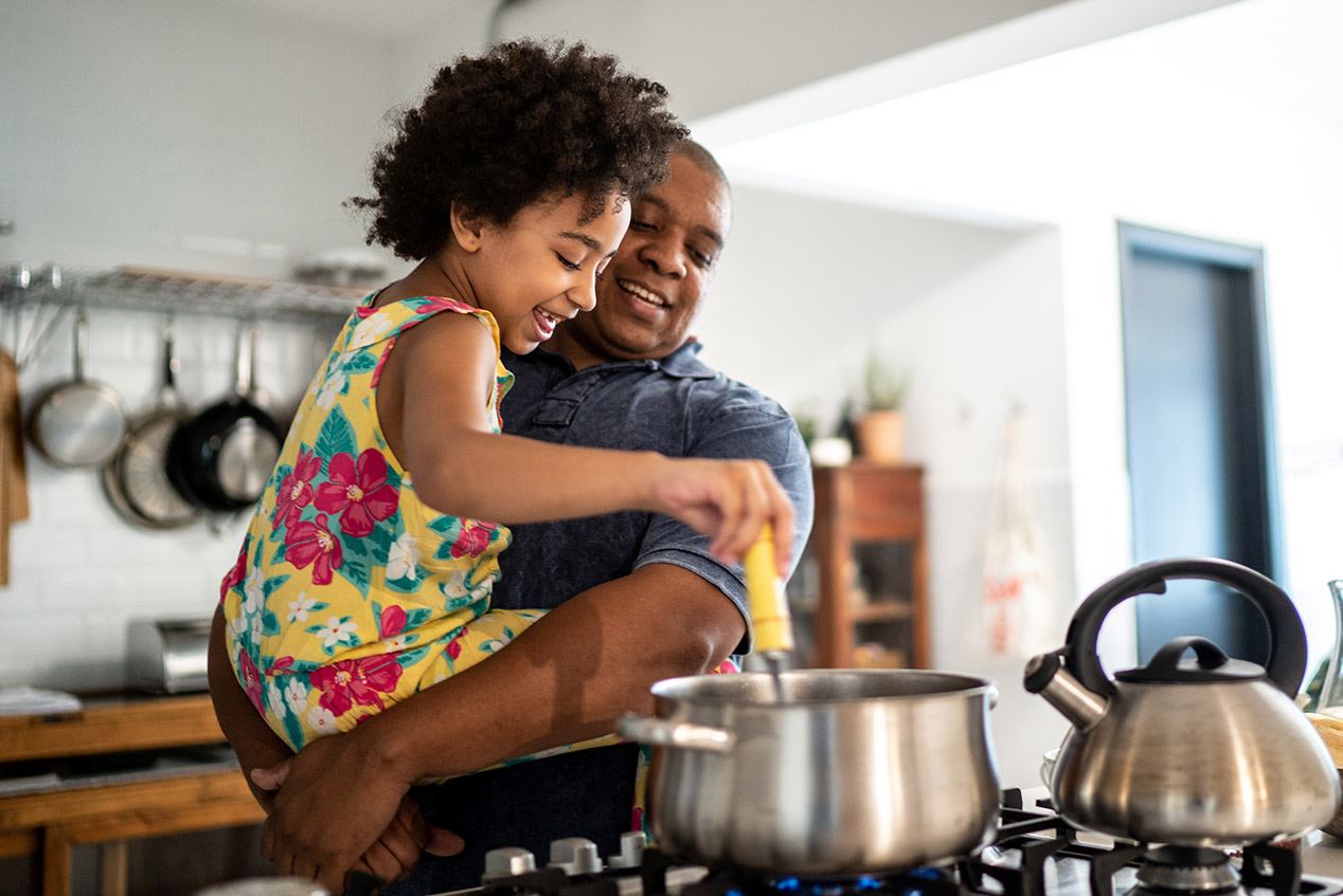 father and daughter making dinner in kitchen