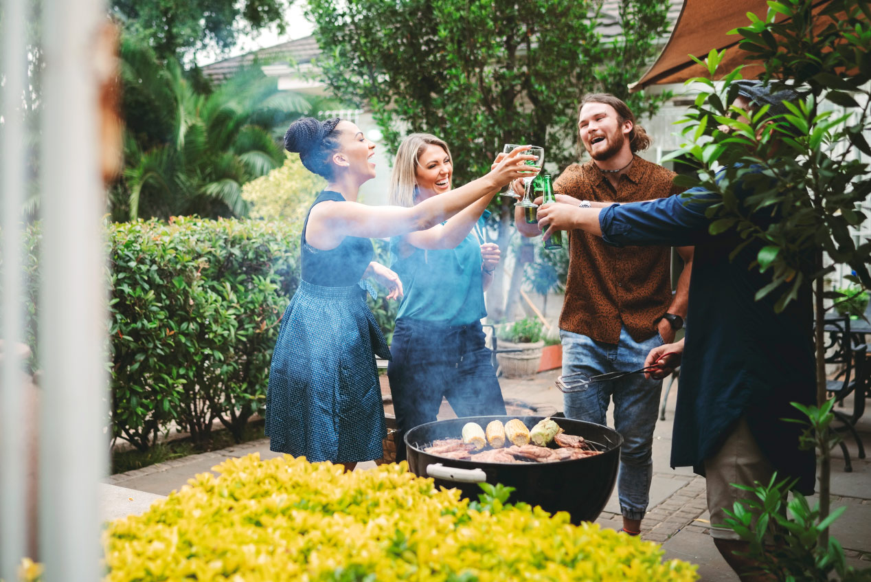 friends grilling out and toasting drinks in the backyard