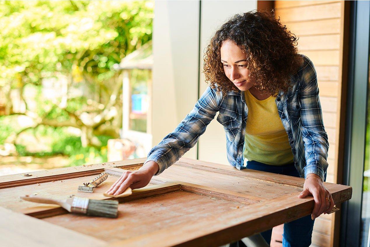 woman sanding a door