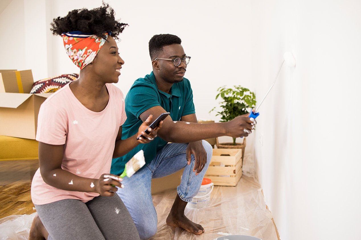 couple painting the wall in living room