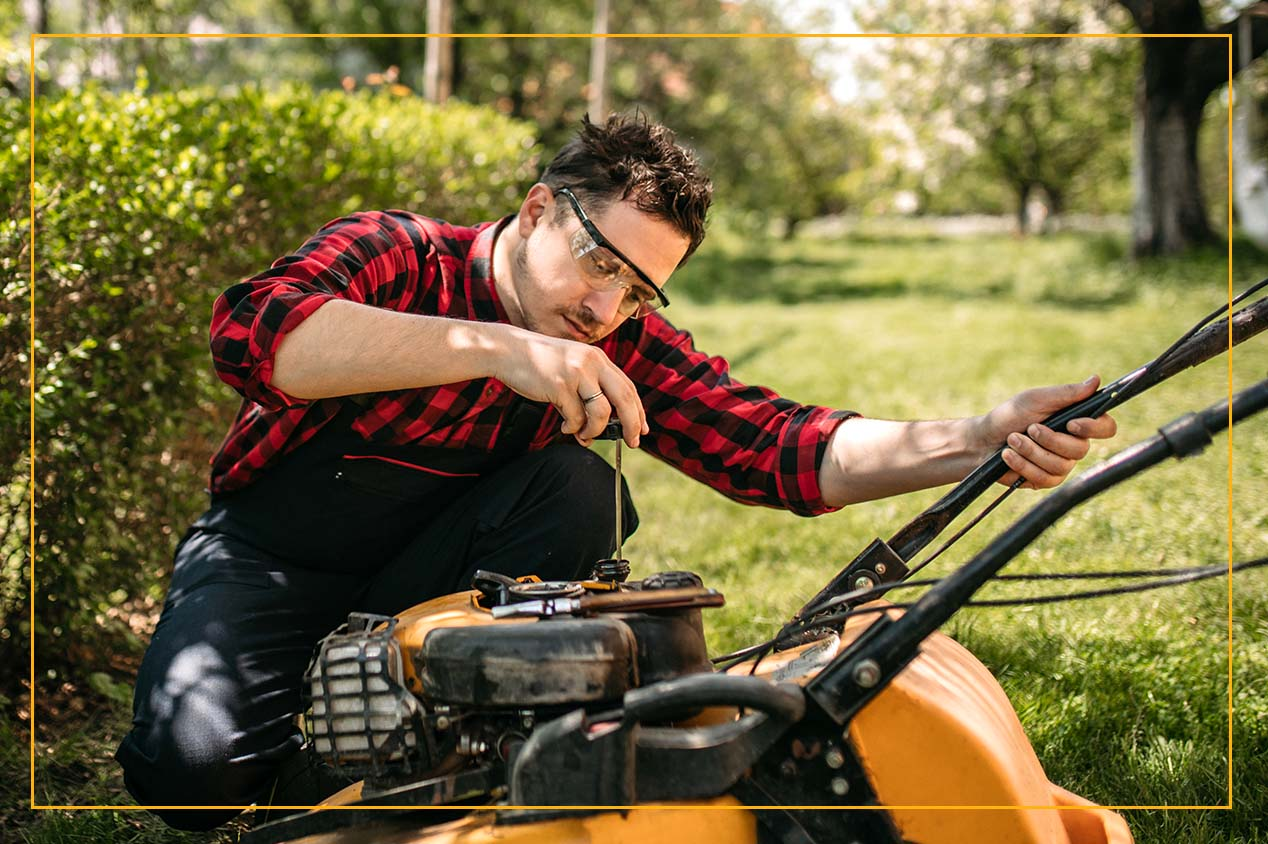 man with protective glasses on prepping a lawn mower