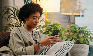 Woman lounging on couch looking at her phone
